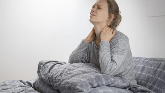 Dolori cervicali: donna che si sveglia con dolori al collo